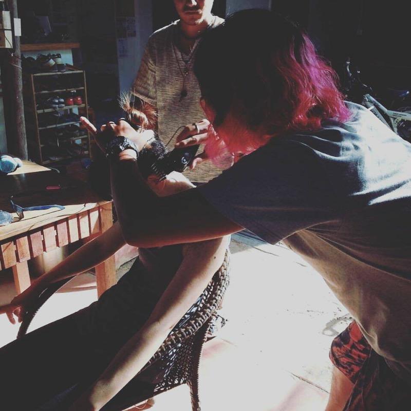 緑の髪の毛の人の髪を切るピンクの髪の人