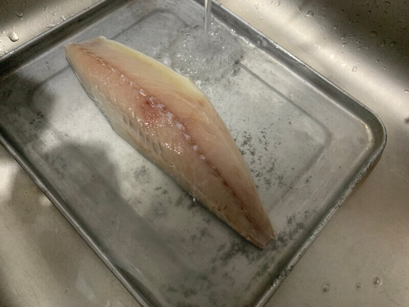 水洗いしている鯖